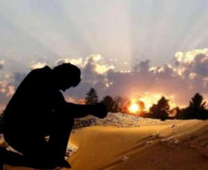 Image of a Pastor praying against a sunset.